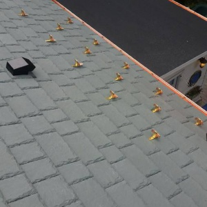 copper_snow_guards_installed_on_synthetic_slate_roof